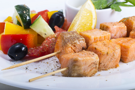 assorted fresh vegetables with chopped red fish on wooden skewers