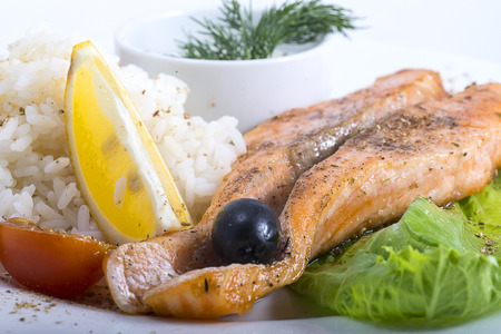 fish with rice and vegetables on a plate closeup