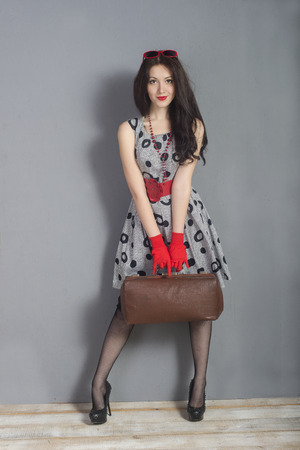 brunette girl with a suitcase and red gloves in gray wall