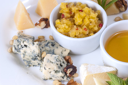 Variety of cheeses on a white plate with sauce and spices closeup  Stock Photo