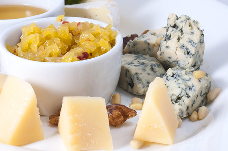 variety of cheeses on a white plate with sauce and spices close-up with shallow depth of field.