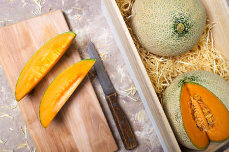 melons in a wooden box in straw. pieces of melon with a knife on the board. Stockfoto