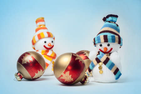 Snowmen with Christmas balls on blue background photo