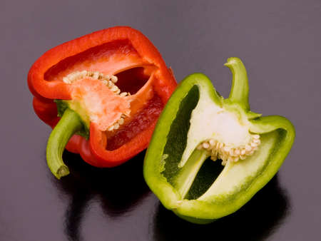 green peppers: A red and green pepper cut in half and placed side by side on a black background. .  Stock Photo
