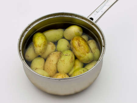 Scrubbed potatoes with skin for healthy eating in pan ready for boiling. photo