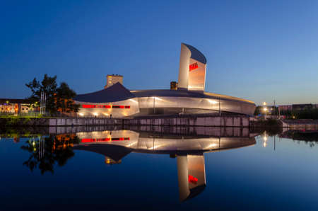 Imperial War Museum North, Salford Quays, Salford, Manchester, England, UK, 10th August 2017. The Imperial War Museum North is an Iconic futuristic building shot at dust showing its refection on the surface of calm water. The building was designed by Dani 報道画像
