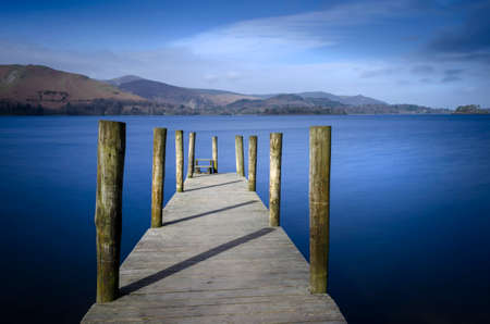 Ashness Bridge jetty on Derwentwater showing a calm Lake and blue sky in the Lake district National park England.