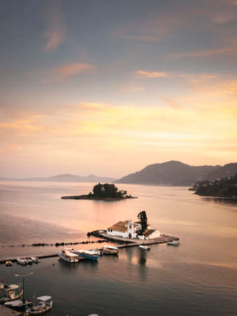 A view of Mouse Island with the 17th century church of Panagia Viacheme in the foreground. The image describes mouse Island and the church just as the sun is sinking behind the mountains of Corfu Greece leaving a golden glow. .