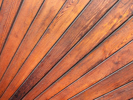 Wooden planks spread out in the shape of a fan with the red wood giving a pattern with texture