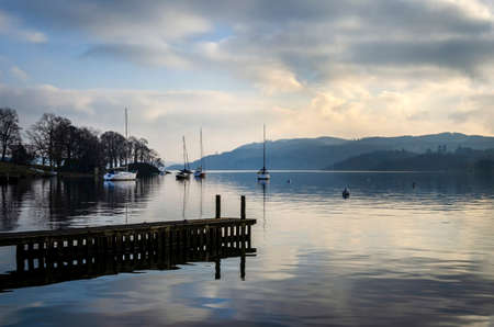 A still quiet peaceful evening at Lake Windermere showing a pier boats and a calm lake.