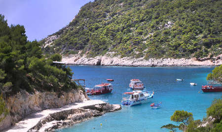 A small Greek harbour where tourist boats wait to collect passengers for excursions. Stock Photo