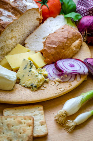 A vertical shot of a delicious quick snack of a ploughman's lunch with fresh bread a variety of cheese and a fresh tomato and an apple. Stock fotó