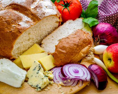 A horizontal shot of a delicious quick snack of a ploughman's lunch with fresh bread a variety of cheese and a fresh tomato and an apple.