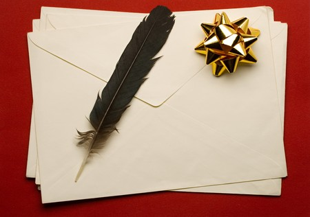 Envelope with ribbon and feather isolated on red background  photo
