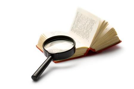 Vergroot glas en boek geïsoleerd op wit Stockfoto