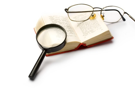 Book, magnifying glass and glasses isolated on white photo