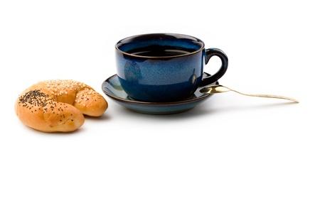 Mug and bun isolated on white photo
