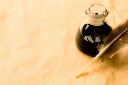 ink bottle: Feather and ink bottle isolated on paper background