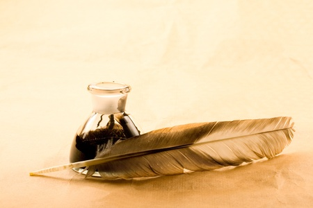 writing on glass: Feather and ink bottle isolated on paper background