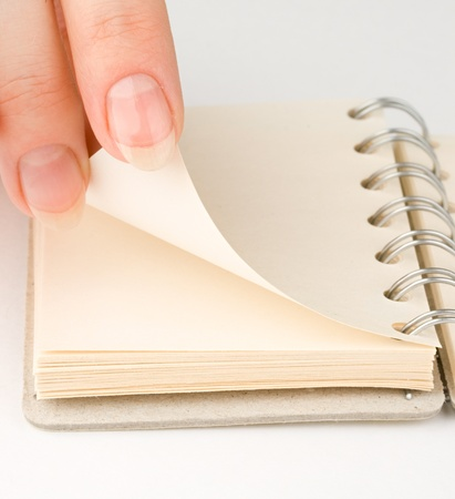Hand and notepad isolated on white photo
