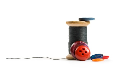 Thread bobbin and buttons isolated on white background photo