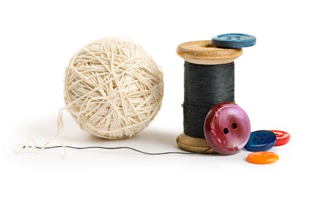 Thread bobbin, ball and buttons isolated on white background photo