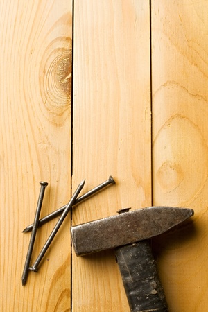 Hammer and nails isolated on wooden background photo