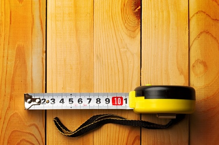 in distance: Tape measure isolated on wooden background Stock Photo