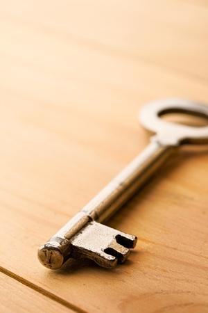 Key isolated on wooden background photo