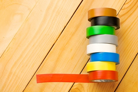 Insulation tape isolated on wooden background photo