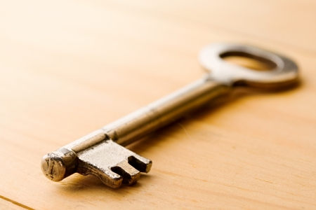 Key isolated on wooden background Stock Photo