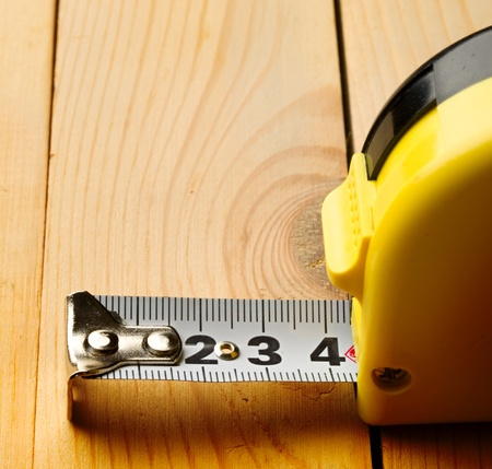 Tape measure isolated on wooden background photo