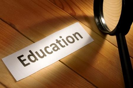 educacion: Lupa aislada sobre fondo de madera  Foto de archivo