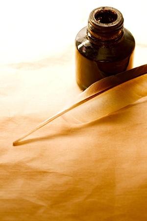 pluma de escribir antigua: Botella de pluma y tinta en el fondo de papel  Foto de archivo