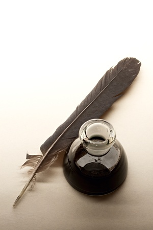 inkstand: Feather and ink bottle isolated on paper background