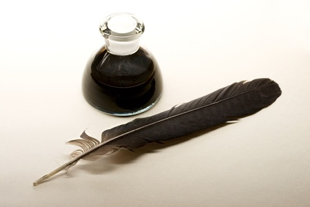 Feather and ink bottle isolated on paper background Stock Photo - 9507296