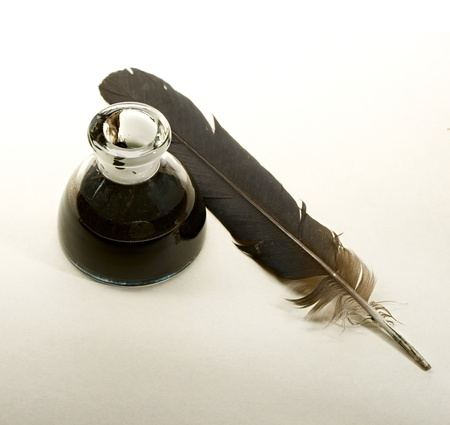 feather quill: Feather and ink bottle isolated on paper background