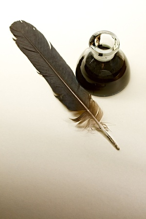 poet: Feather and ink bottle isolated on paper background