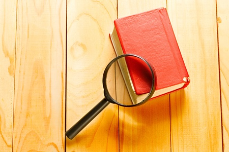 Magnifying glass and book o the wooden background photo