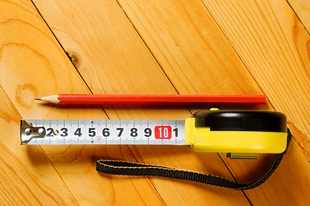 Tape measure, pencil isolated on wooden background  photo