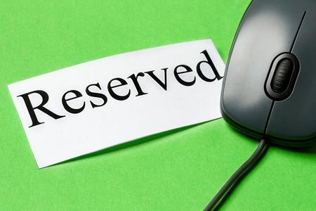 reservacion: Rat�n de ordenador y tarjeta aislados en el fondo verde