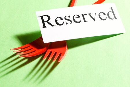 reserved: Forks and card on green background