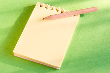 Notepad and pencil on the green background photo