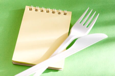 Fork, knife and notepad isolated on green background photo