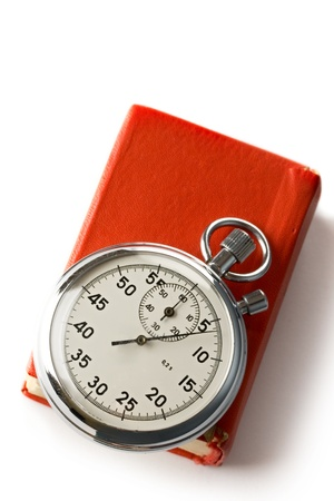 Stopwatch and book on the white background photo