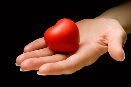 corazon en la mano: Coraz�n en la mano aislada sobre fondo negro Foto de archivo