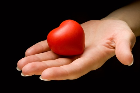 Heart in hand isolated on black background Stock Photo - 10831463