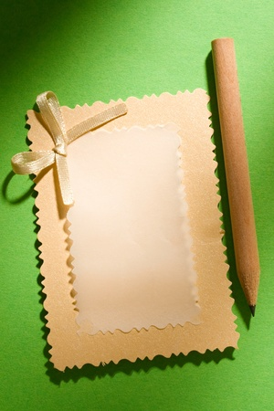 Greeting card and pencil isolated on the green background photo