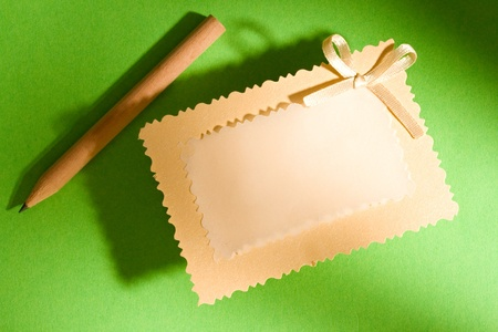 Greeting card and pencil isolated on the green background Stock Photo - 10831408