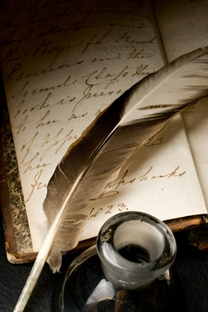 Old book with feather and inkpot  photo